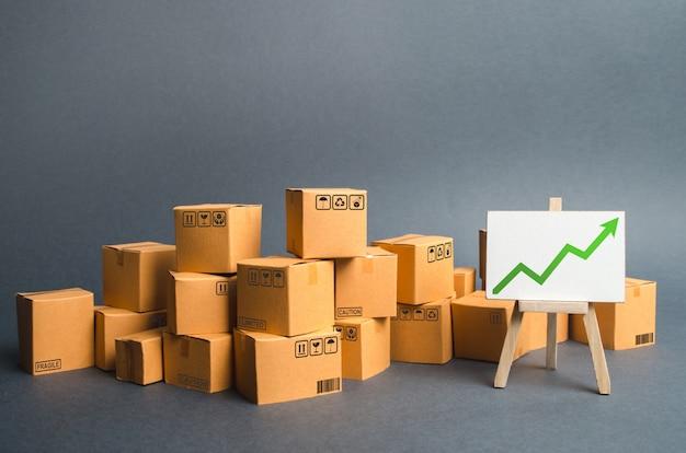 Dużo kartonów i stojak z zieloną strzałką w górę. tempo wzrostu produkcji towarów