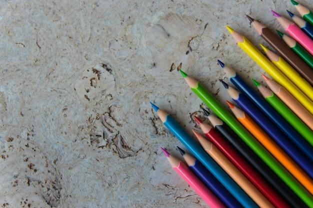 Dużo kolorowych kredek na jasnym tle z naturalnego korka. zarys projektu. miejsce na tekst.