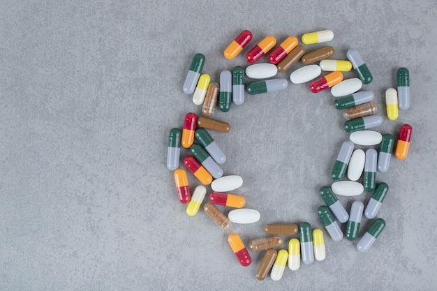 Dużo kolorowych mieszanych tabletek na szarej powierzchni