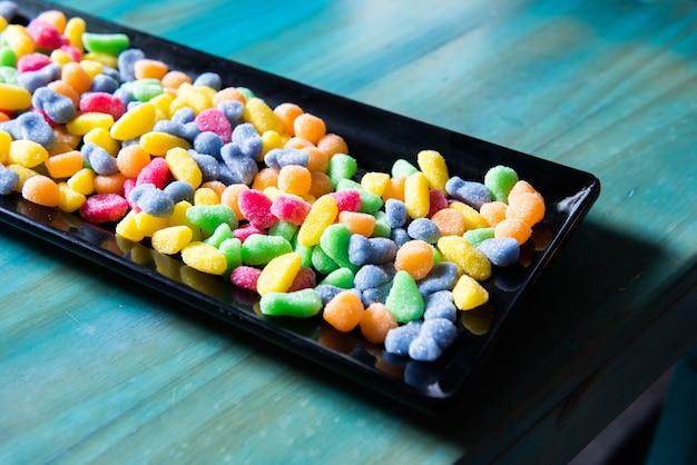 Dużo kolorowych żelków, słodyczy i cukierków, na czarnej tacy na stole, na przyjęciu urodzinowym.