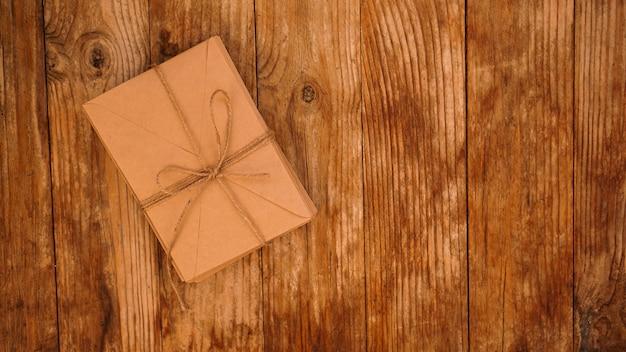 Dużo kopert z papieru kraft przewiązanych sznurkiem na drewnianym tle