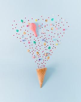 Dużo małych balonów konfetti w czerwone serca i innych rekwizytów imprezowych kornet pastelowe niebieskie tło