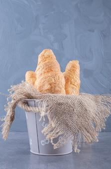 Dużo pieczonego pełnoziarnistego croissanta w koszyku.