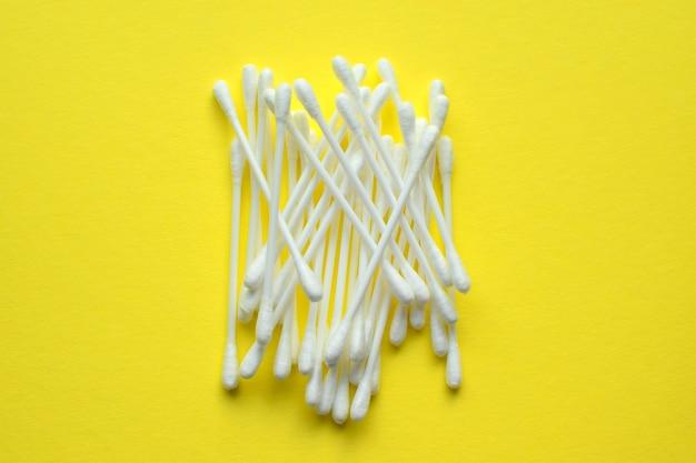 Dużo plastikowych wacików na żółtym tle