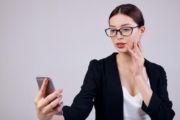 Dużo pracować. zajęty pracownik. przyjemnie wyglądająca spokojna kobieta z telefonem komórkowym w prawej ręce stoi na szarym plecach w czarnej kurtce, białej koszulce i okularach komputerowych.