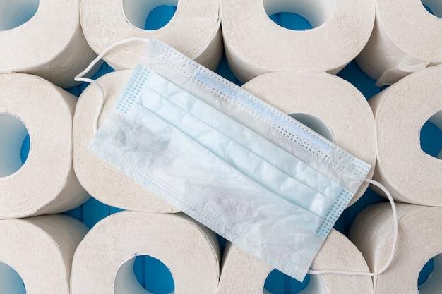 Dużo rolek papieru toaletowego i medycznej maski ochronnej z bliska. izolacja, koncepcja kwarantanny covid-19.