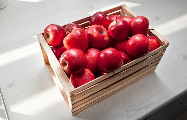 Dużo soczystych czerwonych jabłek w drewnianym pudełku na drewnianym stole w kuchni