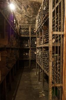 Dużo starych butelek wina w sieci w piwnicy z winami na półkach