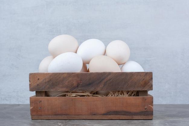 Dużo świeżych białych jaj kurzych na koszu. zdjęcie wysokiej jakości
