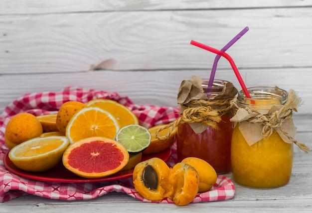 Dużo świeżych owoców, pocięte na drewnianej ścianie, napój, zdrowa żywność