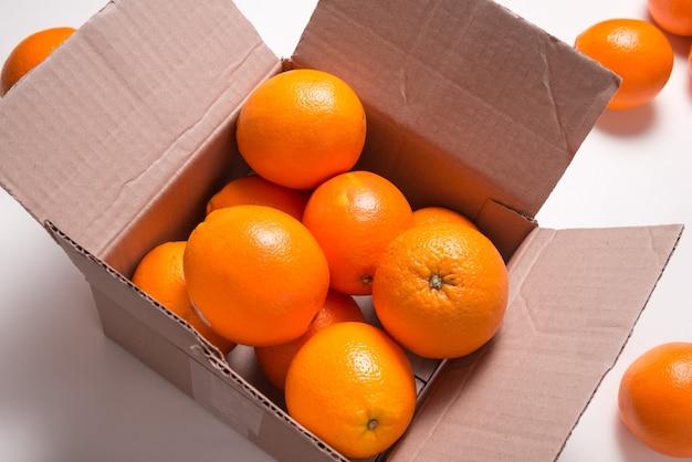 Dużo świeżych pomarańczy cytrusowych w kartonowym pudełku, widok z góry