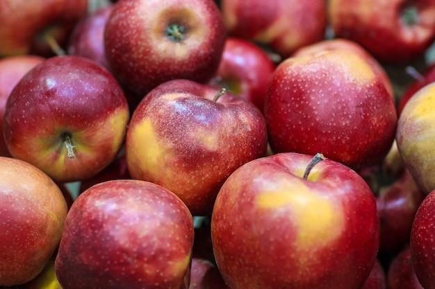 Dużo świeżych pysznych czerwonych jabłek jako tło.