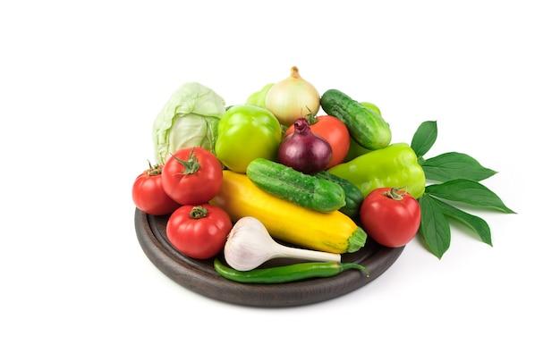 Dużo świeżych warzyw na drewnianej desce z zieloną gałązką z liśćmi.