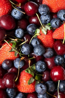 Dużo truskawek, wiśni i jagód. soczyste lato tło z owocami.