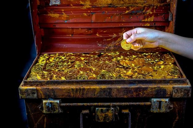 Dużo układania złotej monety w dłoni damy i skrzyni skarbów na czarnym tle