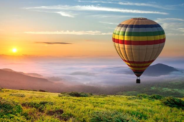 Duży balon na ogrzane powietrze nad zieloną trawą