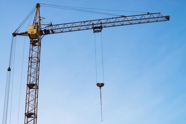 Duży basztowy żuraw przeciw niebieskiemu niebu. tło wizerunek budowy wyposażenia zakończenie z kopii przestrzenią. budowa miasta.
