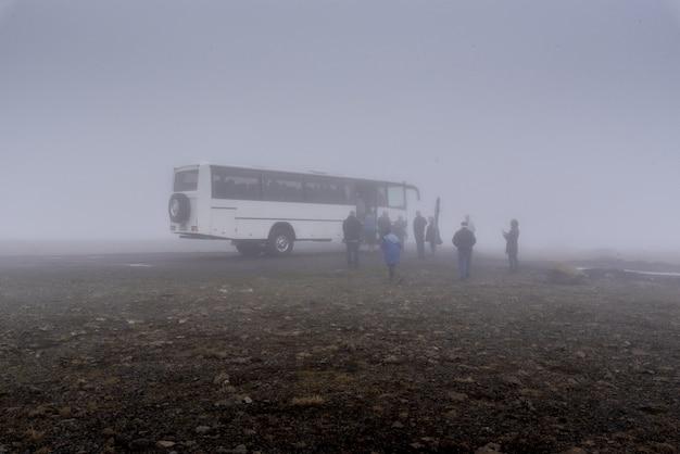 Duży biały autobus i grupa ludzi w jego pobliżu przy mglistej pogodzie na islandii