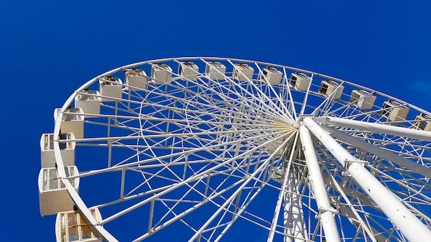 Duży biały diabelski młyn na tle błękitnego nieba. część atrakcji na niebieskim tle z miejsca na kopię. kabiny, platformy widokowe.