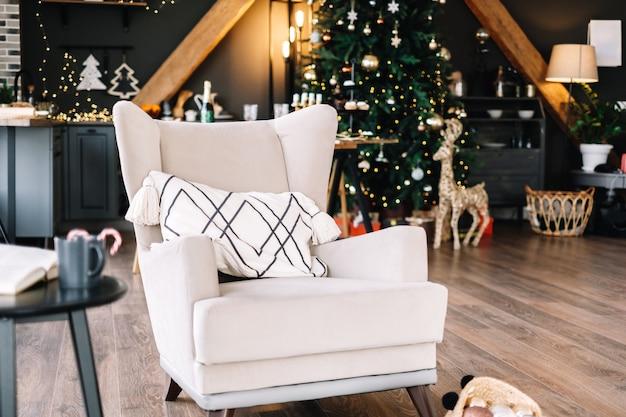 Duży biały fotel w salonie z choinką.