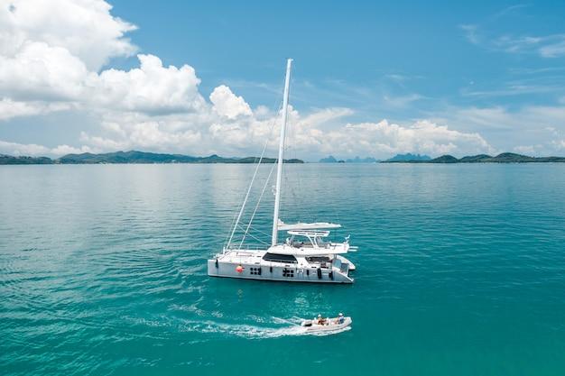 Duży biały jacht pływający w ciepłym lazurowym oceanie, obok którego pływa mała łódka, pozostawiając za sobą fale. pływające statki. czas odpoczynku. przyjemność. drogie wakacje. zdjęcie z kwadrokoptera.