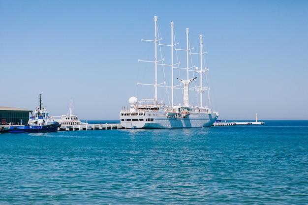 Duży biały jacht z żaglami w pobliżu molo w kusadasi, turcja. koncepcja podróży