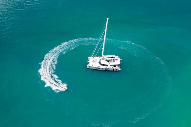 Duży biały jacht żeglujący po ciepłym lazurowym oceanie, obok którego dryfuje mała łódka, pozostawiając za sobą fale. pływające statki. czas odpoczynku. zdjęcie z góry. drogie wakacje. zdjęcie z kwadrokoptera.