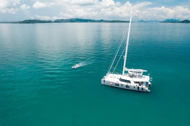 Duży biały jacht żeglujący po ciepłym lazurowym oceanie, obok którego pływa mała łódka, pozostawiając za sobą fale. pływające statki. czas odpoczynku. przyjemność. drogie wakacje.