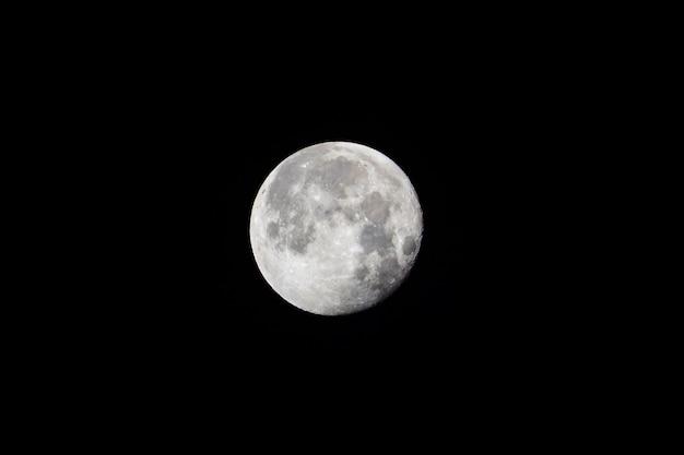 Duży biały księżyc w pełni na czarnym nocnym niebie