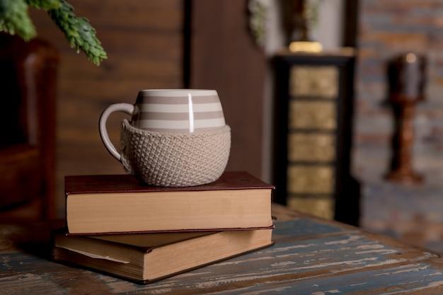 Duży biały kubek na książki na drewnianym stole selektywne focus, vintage filtr. gorąca kawa lub herbata, kakao, filiżanka czekolady na książki z miejsca kopiowania. stos książek, kubek na stole w bibliotece