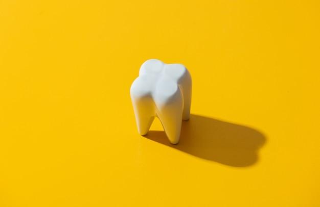 Duży biały ząb na żółtej powierzchni