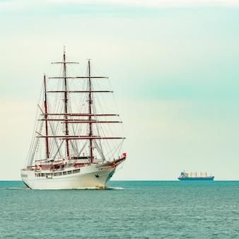 Duży biały żaglowiec z trzema masztami płynący do portu w rydze
