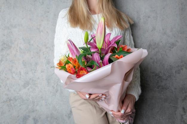 Duży bukiet lilii w rękach dziewczynki