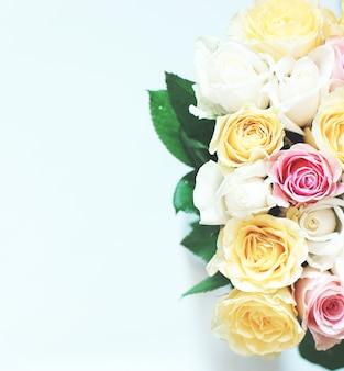 Duży bukiet wielu pięknych różnokolorowych róż na białym tle.