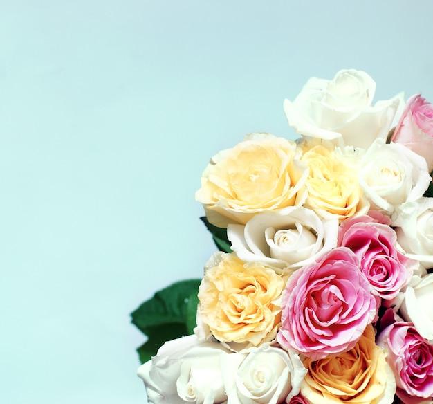 Duży bukiet wielu pięknych różnokolorowych róż na jasnoniebieskim tle.