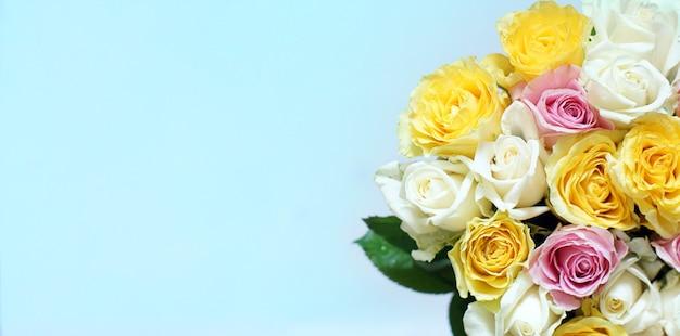Duży bukiet wielu pięknych różnokolorowych róż na niebieskim tle.