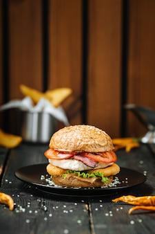 Duży burger na czarnym talerzu ciemny drewniany stół