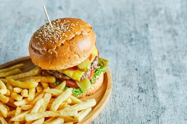 Duży burger ze smażonym ziemniakiem na drewnianym talerzu na marmurowym stole.