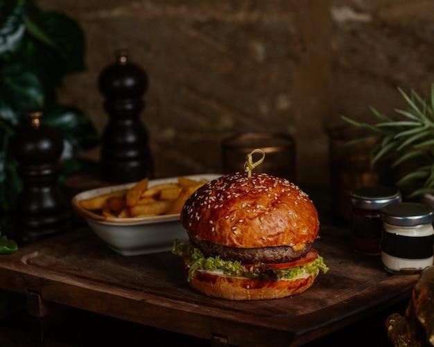 Duży burger ze stekiem i frytkami z ziołami