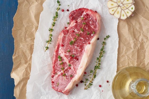 Duży cały kawałek surowego mięsa wołowego, striploin na białym pergaminie na rzemiośle