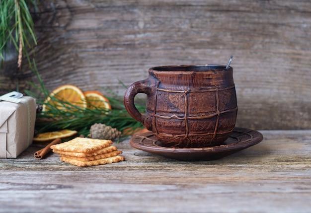 Duży ceramiczny kubek do kawy i krakersy na drewnianym stole z sosnowymi gałązkami, suszonymi pomarańczami, szyszkami i przyprawami