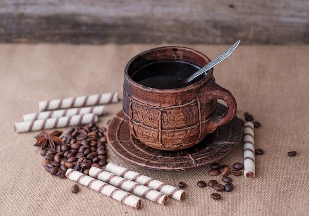 Duży ceramiczny kubek do kawy i wałeczki waflowe na płótnie