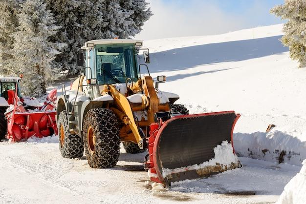 Duży ciągnik z pługiem śnieżnym podczas zimy