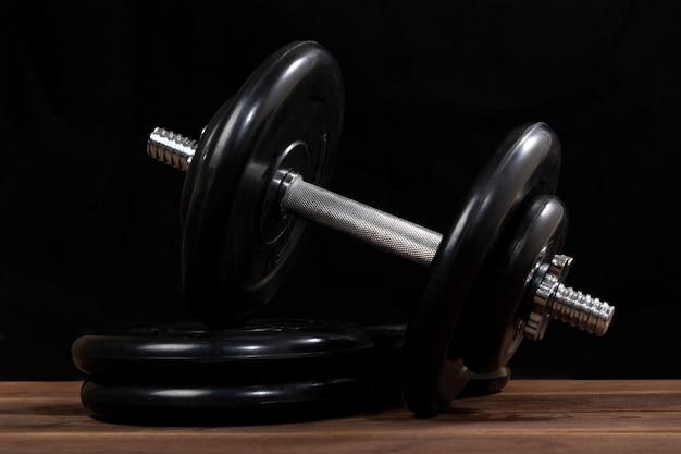 Duży czarny męski dumbbell na brown drewnianym stole na czerni