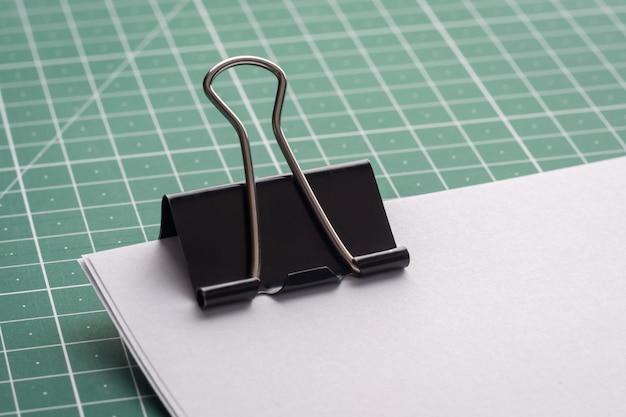 Duży czarny spinacz na stosie papierów na zielonej macie do cięcia