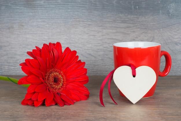 Duży czerwony kwiat z kubkiem kawy i kształt serca na rustykalnym drewnianym stole