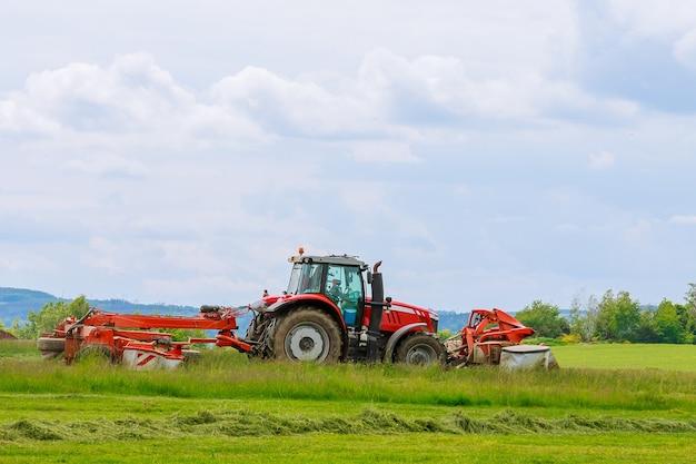 Duży czerwony traktor z dwiema kosiarkami kosi zieloną trawę na silosie.