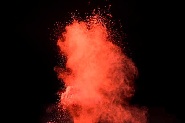 Duży czerwony wybuch proszku na ciemnym tle