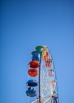 Duży diabelski młyn na tle błękitnego nieba. stoiska z ludźmi idą w górę. jest miejsce na tekst. koncept: rozrywka na wakacjach, wakacje z dziećmi w weekendy, przejażdżki na przejażdżkach.