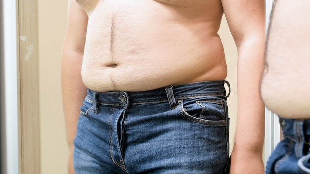 Duży gruby męski brzuch wisi nad małymi dżinsami. pojęcie męskiej nadwagi, odchudzania i diety.